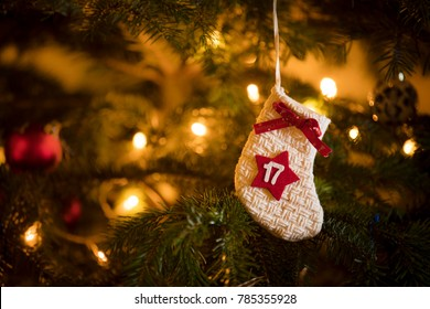 Traditional Advent Calendar Stocking with the date of the 17th of December hanging on a traditional christmas tree.