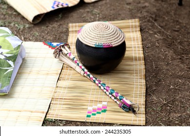 Traditional African calabash with straw cover and drinking tools on grass mat