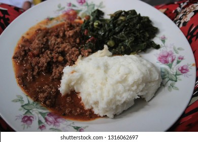 Traditional African cuisine for poor people - cornmeal porridge (Maize or Ishim) with spinach and meat