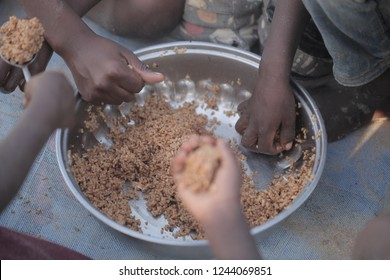 traditional african food: horizontal photography of a silver bowl full of rice dish, with black kids hands eating, outdoors on a sunny day in the Gambia, Africa