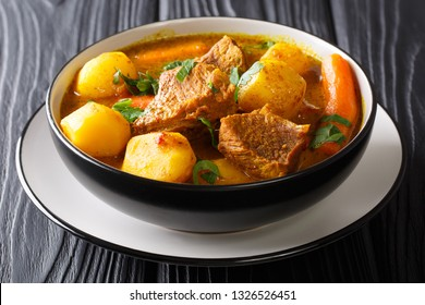 Traditional African slow lamb stew with vegetables and spices close-up in a bowl on the table. horizontal