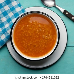 Traditional alphabet soup pasta on turquoise background