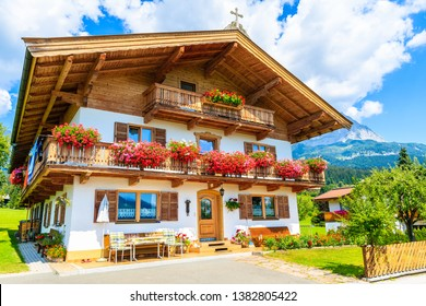 Traditional alpine house decorated with flowers in village of Going am Wilden Kaiser on beautiful sunny summer day, Tirol, Austria