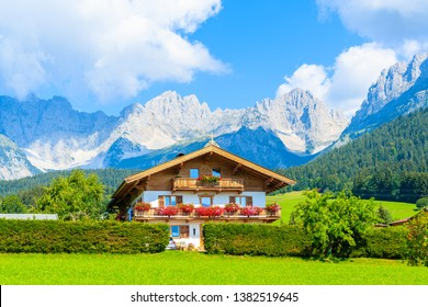 Traditional alpine house on green medow with Alps mountains in background in village of Going am Wilden Kaiser on beautiful sunny summer day, Tirol, Austria