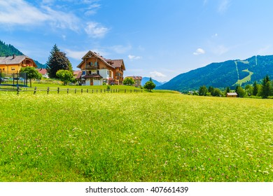 Traditional alpine houses on shore of Weissensee lake in summer landscape of Carinthia land, Austria