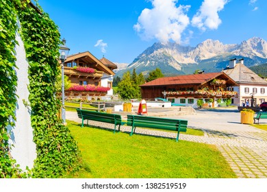 Traditional alpine houses on square in village of Going am Wilden Kaiser on beautiful sunny summer day with Alps mountains in background, Tirol, Austria