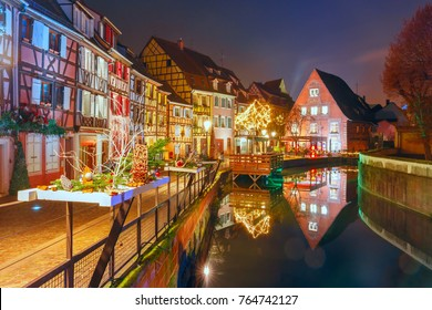 Traditional Alsatian half-timbered houses in Petite Venise or little Venice, old town of Colmar, decorated and illuminated at snowy christmas night, Alsace, France