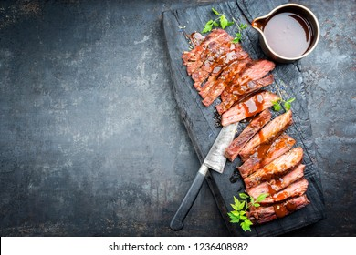 Traditional American barbecue dry aged flank steak sliced with hot sauce and chili as top view on an old carbonized board with copy space left