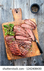 Traditional American barbecue dry aged flank steak sliced as top view on a wooden board