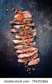 Traditional American barbecue dry aged flank steak sliced with a relish as close-up on a board