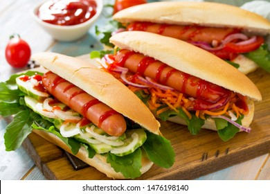 Traditional american fast food. Barbecue grilled Hot dog with fresh vegetables on wooden table.