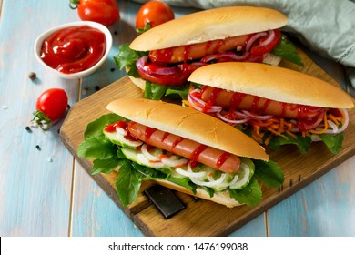 Traditional american fast food. Barbecue grilled Hot dog with fresh vegetables on wooden table with copy space.