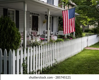 A traditional American home with a white picket fence and flag waving in a small town.