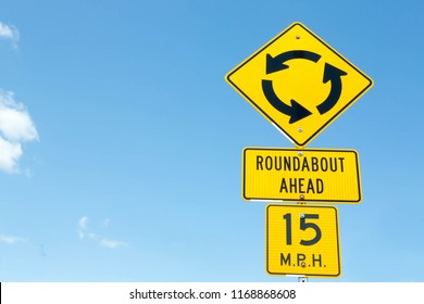 Traditional American roundabout ahead road warning sign