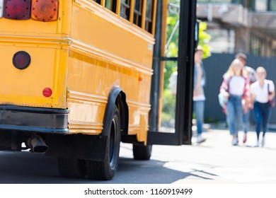 traditional american school bus with group of students walking blurred on background