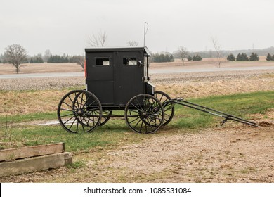 A traditional Amish style horse-drawn buggy parked in a rural countryside setting.