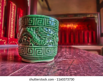 Traditional ancient green cup or bowl with dragon design in front of red interior taiwanese Confucius temple in Tainan