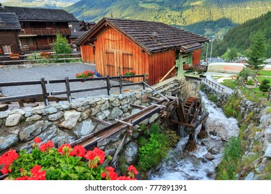 Traditional ancient sawmill with water wheel and river in the picturesque village of Grimentz, Switzerland, in summer