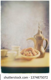 Traditional antique Arabic coffee pot and bowl of dates. Old, grunge vintage photo effect of Middle Eastern food and beverage.