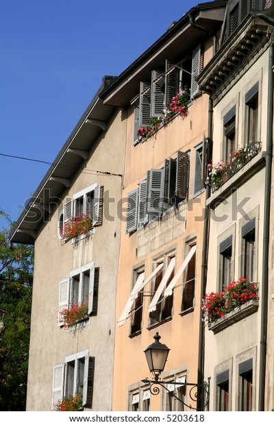 Traditional apartment house with flowers in windows in Geneva Switzerland