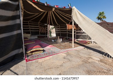 Traditional Arab tent filled with carpets for relaxing on a hot day