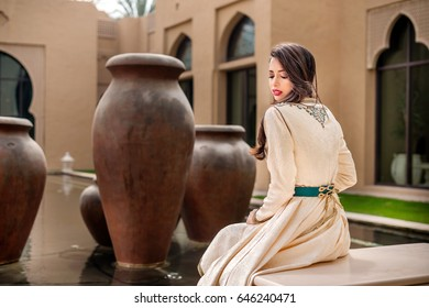 Traditional Arab woman in traditional  Moroccan dress sitting in arabic pool and looking back with the water on background. Ramadan holiday theme.