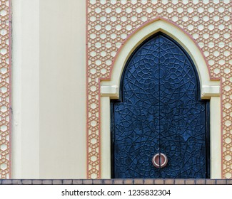Traditional arabesque pattern on the wall, arched iron door with decorative ornament, Islamic architecture, vintage details, background with oriental decor.