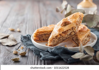 Traditional arabic dessert baklava with  cashew, walnuts and cardamom with an eucalyptus branch on a wooden table. Homemade baklava with nuts and honey.