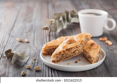 Traditional arabic dessert baklava with a cup of coffee, cashew, walnuts and cardamom with an eucalyptus branch on a wooden table. Homemade baklava with nuts and honey.