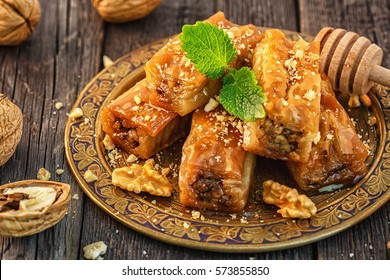 Traditional arabic dessert Baklava with honey and walnuts, selective focus.