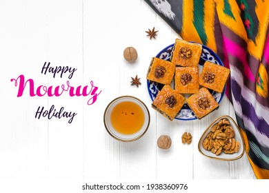 Traditional arabic dessert baklava with walnuts, raisins on plate, bowl, teapot with Uzbek national ornament on white wooden table Text Happy Nowruz Holiday Concept of spring came Top view Flat lay