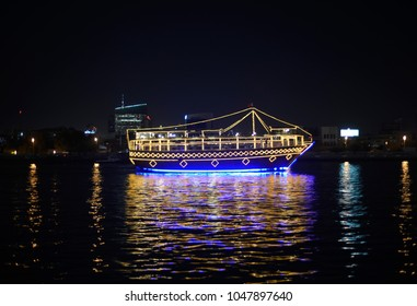 A traditional Arabic dhow illuminated with lights, cruising in the sea, United Arab Emirates.