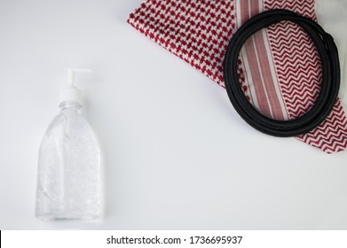 Traditional Arabic dress (especially in Saudi Arabia). Ghutrah also known as the Kuffiyeh or Shmagh along with sanitizer battle as life style during viruses pandemic on white background.