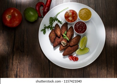 Traditional arabic food, kibes served on white plate, accompanied by salad, ketchup, mustard, pepper and lemon on rustic wooden table