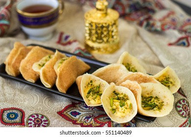 Traditional Arabic kataif crepes stuffed with cream and pistachios, prepared for iftar in Ramadan on paisley background