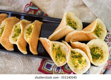 Traditional Arabic kataif crepes stuffed with cream and pistachios, prepared for iftar in Ramadan on paisley background above.