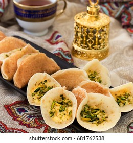 Traditional Arabic kataif pancakes stuffed cream and pistachios Prepared for iftar in Ramadan, oud in gold, on paisley background Square image