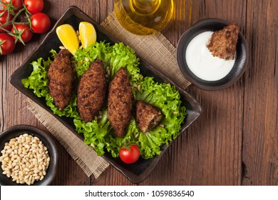 Traditional arabic kibbeh with lamb and pine nuts. Top view. Natural wooden background.