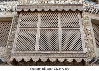 Traditional Arabic mashrabiya balcony enclosed with carved wood latticework in Doha, Qatar.