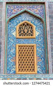 Traditional Arabic mashrabiya window on a tiled wall enclosed with carved wood latticework in Qatar.