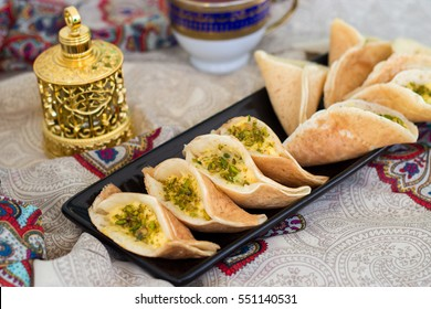 Traditional Arabic qatayf crepes stuffed with cream and pistachios, prepared for iftar in Ramadan on paisley background.