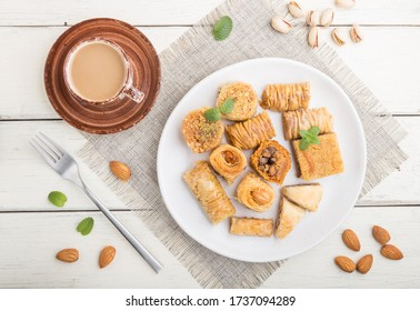 traditional arabic sweets (kunafa, baklava)  and a cup of coffee on a white wooden background and linen textile. top view, flat lay, close up.