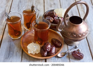 Traditional arabic tea with dry madjool dates and rock sugar nabot. Selective focus.