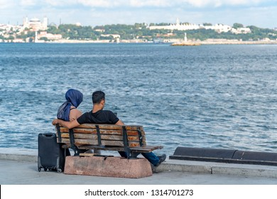 traditional arap girl and boy sitting at seafront, enjoing the sky line of istanbul with great view to the agia sophia and the topkapi museum, a short escape from the travel hassle