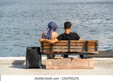 traditional arap girl and boy sitting and chatting at seafront, enjoing the nice weather, finding peace from the serenity of the sea. a short escape from the travel hassle
