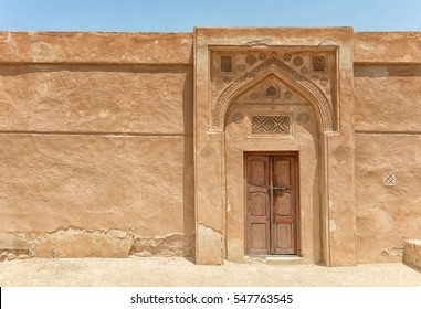 A traditional arched doorway with gypsum carvings and a carved door stands in bright sunlight in a wall of Riffa Fort, Bahrain, in the Arabian Gulf.