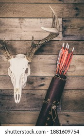 A traditional archery hunting scene with quiver of arrows and buck antlers.