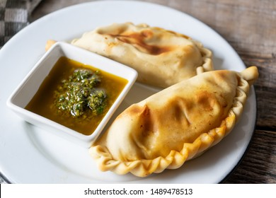 Traditional Argentine empanadas with chimichurri sauce on wooden background