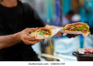 Traditional Argentine Fresh cooked sandwiches with meat and herbs in the hands of a man.