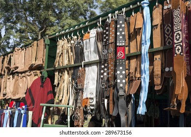 Traditional Argentinean leather gaucho belts, boots and cinchs hanging on for sale on a fair in Rosario city, Argentina